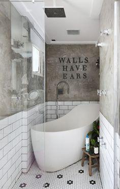 Cimento queimado e pastilhas hexagonais compõem um banho luxuoso