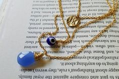 This layered necklace features a wire wrapped Czech glass faceted tear drop with an evil eye bead and gold coin charm. The Evil Eye is said to be a curse of sickness and injury cast by a malevolent glare. Talismans against the Evil Eye are also named as such and is found in several Muslim, Jewish, and Christian cultures. This necklace serves as a talisman of protection against the Evil Eye in addition to adding a unique feature to your jewelry collection.  Care instructions: Do not swim…