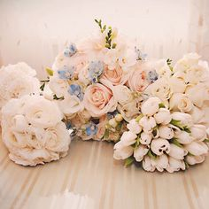 Bridal bouquet of roses, lisianthus, ranunculuses, and blue tweedier. Photo by Jessica Horwitz Photography