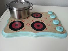 After seeing multiple pins about minimalist play kitchens,  I set out to make my own.  I made this stove out of a wood plaque from and some wooden toy wheels from Hobby Lobby.  I painted the plaque and mod podged scrapbook paper and paper circles for the burners.  I loosely screwed in the knobs so they could still turn.  Finally, I gave it a vintage look using distressing ink. Total cost was a little over $5.