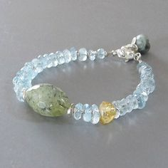 Gorgeous sparkling pale irregular hand cut slices of Aquamarine alternated with very tiny handmade fine silver beads surround a beautiful prehnite loaded with black rutiles. There is one offset Citrine. It closes with a lobster claw clasp and has a Cats Eye Aquamarine capped in silver petals dropping from the end of the extender chain.  All metal is solid .925-.970 sterling and fine silver.  Aquamarine - approx. 5-8mm Citrine - approx 8mm Prehnite - approx. 20mm  Length - approx. 7 long…