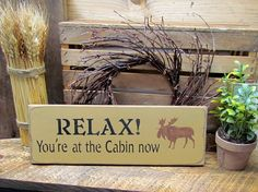 "This wood sign reads ""Relax! Your at the Cabin Now"". With moose It measures roughly 5.5""w x 16""L. It has been painted then sanded and distressed for a great OLD look. It would be a wonderful addition"