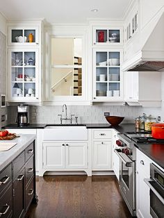 a gorgeous black + white kitchen, love the painted backs of the glass front cabinets