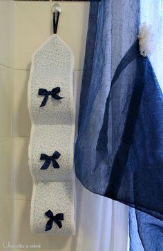 Un tutorial per cucire un porta rotoli in tessuto per il bagno. Con tre spazi per i rotoli, dei fiocchetti decoratini ed un semplice pizzo tutt'intorno.