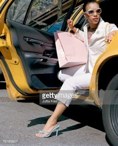 A woman stepping out of a taxi with shopping bags, New York City, USA : Photo