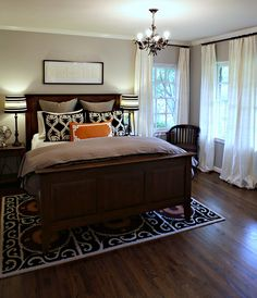 Love this bedroom! A little color on the walls, patterned rug & pillows, long curtains
