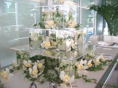 12 Ideas for Events with All White Decor     At Tourism Toronto's client reception in 2007, a three-tiered acrylic structure that was accented with wild white flowers and green vines served as a display for all-white chocolate sushi bites.  Photo: BizBash