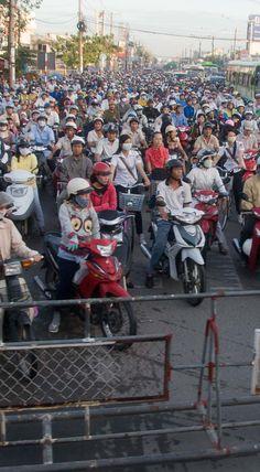 Stau vor dem Bahnschranken in Saigon (Ho-Chi-Minh-Stadt), Vietnam. Wehe, wenn der Zug kommt, dann bringt er den Berufsverkehr komplett zum erliegen. Weitere unglaubliche Bilder mit tausenden Motorrädern und Reisetipps im Blogbeitrag. #zugreise #abenteuer Hanoi, Thailand, Cambodia, Singapore, Travel Report, Travel Inspiration, Adventure