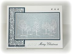 "By Cindy Elam. Focal image: Stamp trees from ""Lovely as a Tree"" in VersaMark on brushed silver cardstock. Heat emboss with silver powder. Sponge with frost white shimmer paint. Mat on white then navy cardstock. Side panel: Dry emboss brushed silver cardstock in ""Petals-A-Plenty"" folder (SU); mat on navy. Stamp sentiment in navy. Attach panels. Add gems."