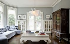 Love the light gray walls and the couch all along the wall #hardwoodfloors #livingrooms #couches #gray #white #windows