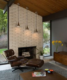 Mid century modern defined through fireplace stonework, furniture design, lighting, natural wood, and clean lines.