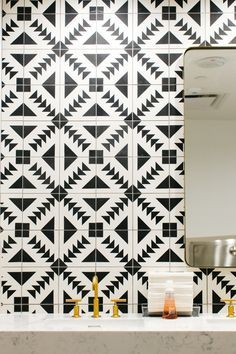 black and white tile with brass fixtures and marble counters /