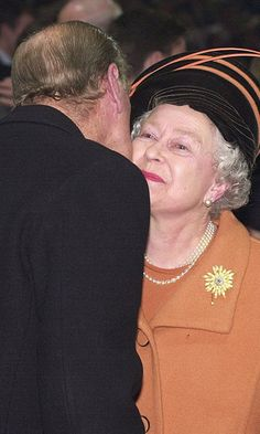 To usher in the new millennium, Prince Philip plants a kiss on his wife during the New Year's Eve celebration at the Millennium Dome in 1999.