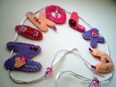 **Jméno..na přání.. Filcová závěsná dekorace..jméno. Vhodné jako ozdoba do dětského pokoje - na dveře, záclony, okno, poličku, stěnu nebo kdekoli kde Vás napadne =). Jako dárek k narození miminka, Svátku.. Materiál: pogumovaný provázek, stužka, filcové písmenka, bavlnky, korálky a perličky, písmenka jsou vyztužené, domalované glitry. Velikost písmenka 3-4 cm, ...