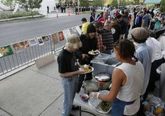 Across from the gala, homeless people line up for dinner. Also in protest, artwork is pinned to a barrier.