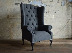 Modern British handmade Nuvo deep buttoned Chesterfield wing back Chair, shown Dark Grey Wool. High back | Abode Sofas
