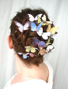 I did this by cutting pictures out of a butterfly book, laminating the cut out butterflies, and gluing them to the end of bobby pins.  Just a couple of them, clipped onto an updo is really lovely.