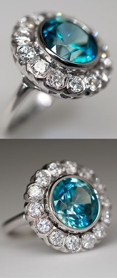 ANTIQUE ZIRCON COCKTAIL RING W/ OLD EURO DIAMOND HALO PLATINUM, Circa 1930s ring is centered with a bezel set round brilliant cut natural blue zircon, surrounded by a halo of fourteen (14), prong set, round transitional brilliant cut diamonds. The ring measures 17.0mm wide at the top, rises 6.0mm above the finger.