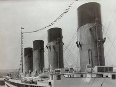 RMS Olympic in bunting and getting her funnels painted