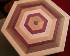 Unique hexagonal design handmade with maple, walnut, cherry, and purpleheart wood is set into a face grain slab of maple. Tight seams, flush on both sides, reversible if desired, with custom cut pocket handles on each side for easy handling. Finished with a blend of food-safe mineral oil and local natural beeswax. DIMENSIONS: 1 x 12 x 17 inches **Shipped with a small bottle of mineral oil and beeswax blend with care instructions.