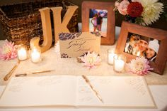 Guest book table, with our initials, a few pictures, flowers, a guestbook, and a sign