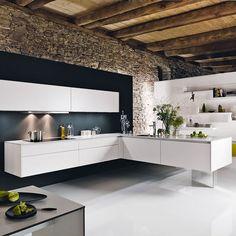 cozinha em forma de L, com paredes expostas de pedra, parede de recurso preta, armários brancos e ilha flutuante