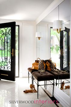 silverwood interiors wrought iron door, panelled mirror wall and sconces on the mirrored wall