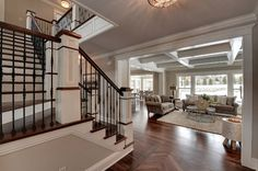 Cool open kitchen, family and foyer with reverse staircase.
