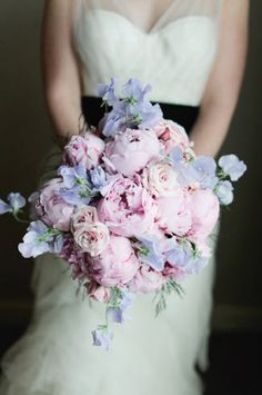 Pretty and delicate pink, mauve, and lavender freeform bouquet of peonies, roses, and sweet peas.