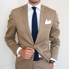 Reach for a camel suit and a white oxford shirt to ooze class and sophistication. Shop this look on Lookastic: https://lookastic.com/men/looks/suit-dress-shirt-tie/20887 — White Dress Shirt — Navy Knit Tie — White Pocket Square — Tan Suit — Brown Woven Leather Belt