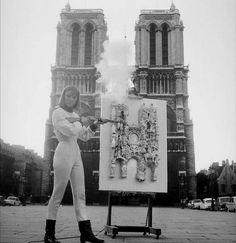 """NIKI DE SAINT PHALLE, UNE """"NANA"""" D'EXCEPTION - Tirs - Niki de Saint Phalle fêtant à sa façon les 800 ans de Notre-Dame de Paris en 1963. Deux ans plus tôt, elle avait commencé la série des """"tirs"""". Elle répand les couleurs en tirant sur des panneaux où sont fixés des objets symboliques et des sacs de couleur. © Delmas / Sipa Press - Publié par Le Point.fr le 29/10/2014 http://www.lepoint.fr/arts/niki-de-saint-phalle-une-nana-d-exception-29-10-2014-1876699_36.php"""