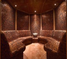 Neutral tiling with copper tones creates a warm and relaxed setting in the steam room at Grand Hyatt Dubai, Ahasees Spa & Club. Designed by HBA/Hirsch Bedner Associates.