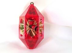 Vintage mid century, red plastic lantern - style Jewel Brite Christmas ornament features a sprig of holly behind two glitter rimmed bells. The