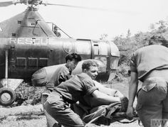 THE KOREAN WAR 1950 - 1953 Medical personnel prepare wounded soldiers for evacuation by helicopter.