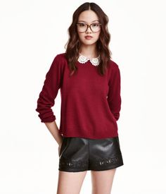 Dark red. Short sweater in a soft, fine knit with a rounded lace collar, long sleeves, and opening at back of neck with button.