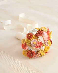 To create blooms in a variety of textures, sizes, and shapes, use ribbons and rickrack in different widths and weaves. The folds of each flower are clustered around artificial stamens; stems are individually wrapped in floral tape before all are bundled together and bound in wide white grosgrain.