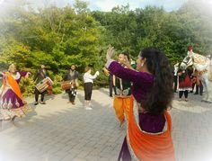 Baraati dancing during Baraat procession at The Manor in West Orange with decorated white horse.
