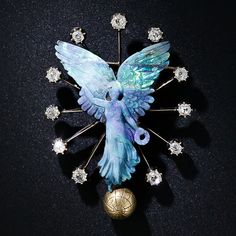 """""""The goddess of Victory - Nike, is divinely handcarved in a glowing, many-splendored opal with her wings aflame. The wreath-bearing deity bestrides a golden globe and is surrounded by a sparkling constellation of old mine-cut diamonds. A truly unique and astonishingly beautiful mid-nineteenth century jewel crafted in 14 karat gold. 2 inches by 3/8 inches."""""""