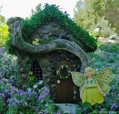 A miniature fairy house with a tiny yellow wreath and little yellow bird in our miniature fairy garden. (Enchanted Gardens)