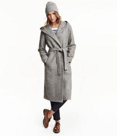 Vuorillinen pitkä takki villasekoitteista bukleeta. Vuorattu huppu ja sivutaskut. Solmittava vyö.