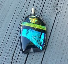Dark Abstract Dichroic Fused Glass Pendant | HCLTreasures - Jewelry on ArtFire, Dichroic glass contains multiple micro layers of metals or oxides. It has a particular transmitted color and a completely different reflected color which causes many colors to be displayed. Depending on the angle of view the colors shift.  A Dark Dichroic Abstract Pendant Lots of Bling to this one. Our base layer is Black and then topped with bits of Lime Green, Blue and Gold Dichroic.