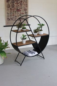 The Metal And Wood Round Shelf features an elegant design with sturdy wooden shelves with round metal frame.Color: Metal frame Material: Metal & Wooden Shelf Round Shape Metal And Wood Round Shelf Dim