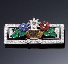 GEM-SET AND DIAMOND PLAQUE BROOCH, CIRCA 1930. The open work rectangular plaque set with lines of circular- and single-cut diamonds and polished onyx, framing a stylised vase set with carved citrine and containing lapis lazuli, carnelian and marquise-shaped diamond flowers and carved chrysophrase leaves.