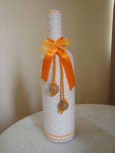 Conjunto de 2 garrafas decoradas com barbante cru, fitas de cetim e cordão na cor laranja e miçangas de madeira. Medidas garrafa maior: 30 cm altura x 10 cm largura Medidas garrafa menor: 22 cm altura x 8 cm largura
