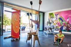 Samuel Rubell with Sculptures (left to right) by Guyton\Walker, Henry Taylor, and Aaron Curry, and a mural-size painting by Neo Rauch, in the open-air living room of his family's art-filled Miami Beach home. The newly constructed house was conceived by DOMO Architecture + Design with interiors by Austin Harrelson | archdigest.com