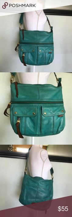 Fossil cross body bag Larger fossil cross body bag. Teal blue with brown accents. One zipper pocket on front with two snap closure pockets. One pocket on back. Top zips closed. Inside has a zipper pocket and two pouches. Cross strap is removable. Shows a bit of wear but no rips holes stains. Height 11.5, width 14.5, depth 2 1/4. Handle at longest 24, shortest 13. Fossil Bags Crossbody Bags
