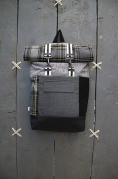 "Black and grey roll top rucksack with a pocket from men's suit jacket in the front , by ""eating the goober"""