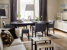 A dining area with a black-brown dining table combined with dining chairs with armrests and footstools, all with dark grey covers.