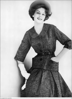Model in suit of black and white houndstooth check silk, the skirt is box-pleated with longer jacket accentuated by low pockets by Gaines-Parnet, jewelry by Trifari, photo by Karen Radkai, Vogue, August 1, 1959