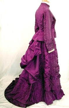 English: 1870s dress, purple silk bodice and skirt with bustle back. Historic costume collections of Southend Museums Service via Wikimedia Commons